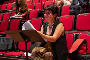 Woman with short brown hair and red glasses sitting on a red chair reading music from a music stand