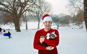 Young man standing in the snow wearing a red sweater and a santa hat, holding a tabby cat in his arms. The cat is wearing a santa outfit.