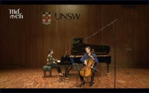 A woman playing a grand piano and a man to the right playing the cello