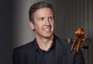 Image of Julian Smiles, smiling and holding his cello