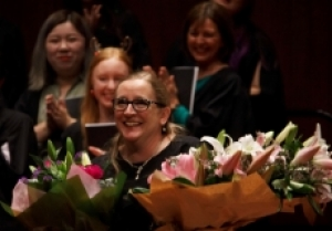 Woman with blonde hair and glasses holding two large bouquets