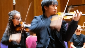 Young man playing violin in an orchestra