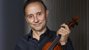 Dene Olding, wearing a black collared shirt and holding a violin