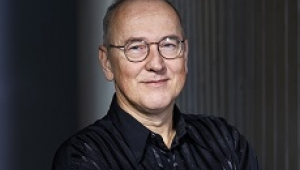 Ian Munro, a man wearing glasses and a black buttonup shirt smiling with his mouth closed