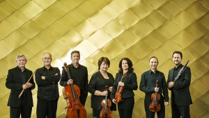 7 members of the Australia Ensemble standing in front of a gold cladded wall holding their instruments