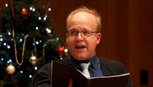Man wearing glasses and holding a black folder while singing in front of a Christmas tree