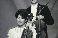A black and white photo of a young man wearing a tuxedo, standing with his violin. In front of this is a young woman, wearing a white frilly dress holding a viola