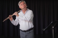 Man in a white shirt with dark grey pants and light grey hair playing the flute