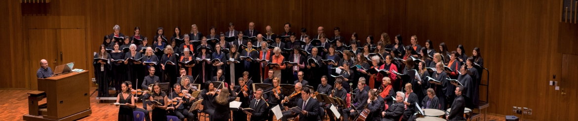 Large choir singing with chamber orchestra on stage