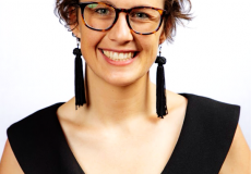 Young woman with short brown hair and glasses weaing long dangly earrings and a black dress